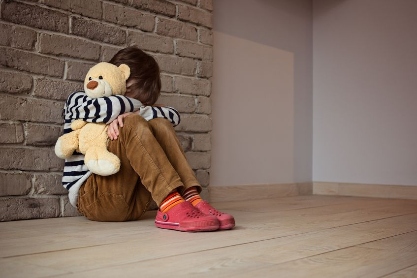 38654273 - sad little boy sitting against the wall in despair. in his hands he holds an old friend teddy bear