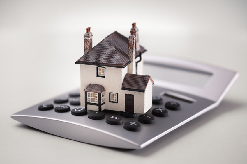 38970066 - house resting on calculator concept for mortgage calculator, home finances or saving for a house